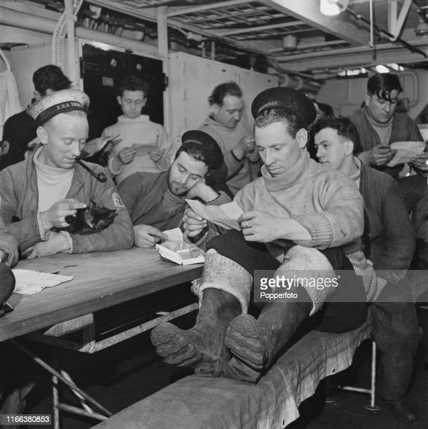 View of Royal Navy submariners reading letters from home on board the Royal Navy T class submarine HMS Tribune after docking with the submarine...