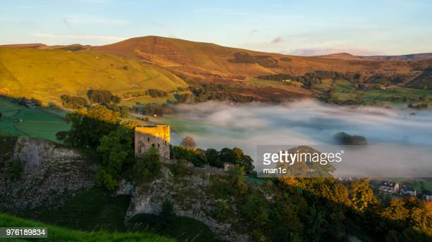 view of ruins of peveril castle in peak district and fog in valley, castleton, derbyshire, england, uk - peveril castle stock pictures, royalty-free photos & images