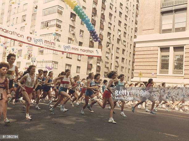 View of runners as they cross the starting line of the L'eggs Mini Marathon at the intersectoion of Central Park West and West 63rd Street late 1970s...