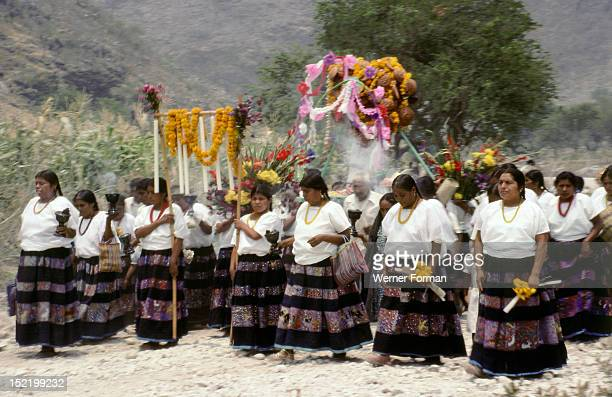 View of rural springtime fiesta at the remote village of Zitlala Guerrero The women wear elaborately embroidered skirts and are carrying a main altar...