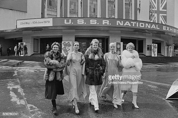 View of Russian male and female models wearing examples of Soviet fashion including furs outside the USSR National Exhibition at Earls Court...