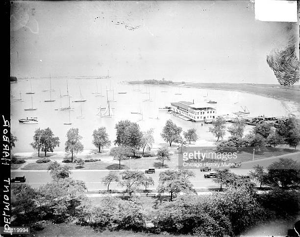 View of sailboats sitting in water in Belmont Harbor located in the Lake View community area of Chicago Illinois 1929 Automobiles are driving along a...