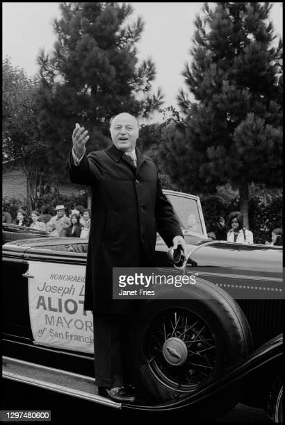 View of San Francisco Mayor Joseph Alioto as he waves from the running board of a convertible during the annual Columbus Day Parade in the North...
