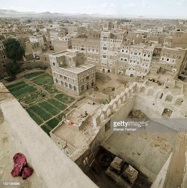 View of San'a, Geometrically incised plasterwork and ornate window arches decorate the facades of the multi-storeyed houses.Gardens in the...