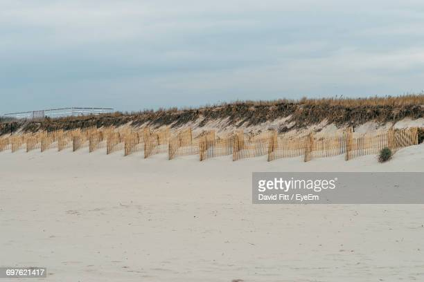 view of sand fences on beach against sky - sag harbor stock photos and pictures