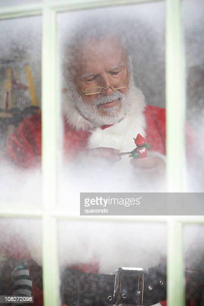christmas scene with frosted window pane and santa claus, copyspace - santas workshop stock photos and pictures
