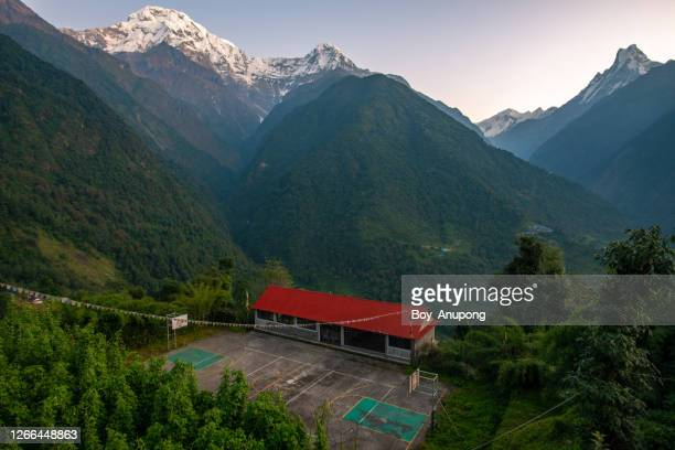 view of school building in ghandruk village with spectacular view of annapurna mountains range in nepal. - annapurna south stock pictures, royalty-free photos & images