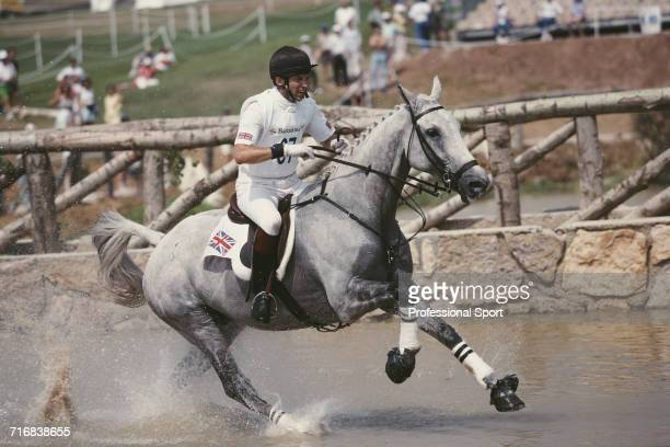 View of Scottish equestrian Ian Stark of the Great Britain team riding Murphy Himself through a water hazard during competition in the cross country...