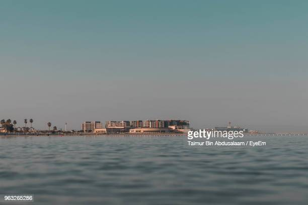 view of sea against buildings in city - bin taimur stock photos and pictures