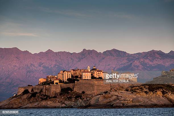 view of sea and calvi on headland at dusk, corsica, france - corsica stock-fotos und bilder