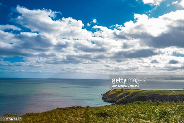 view of sea and lighthouse on peninsula, dublin, republic of ireland - dublin republic of ireland stock pictures, royalty-free photos & images