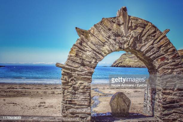 view of sea shore against clear sky - arch stock pictures, royalty-free photos & images