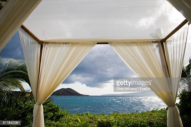 View of sea through curtains