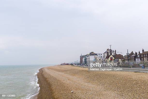 view of sea with buildings in background - deal england stock photos and pictures