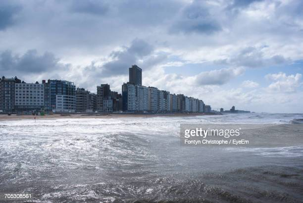 view of sea with buildings in background - オステンド ストックフォトと画像