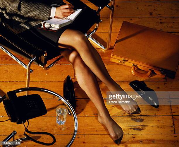 View of seated woman's crossed legs,shoes and briefcase on floor