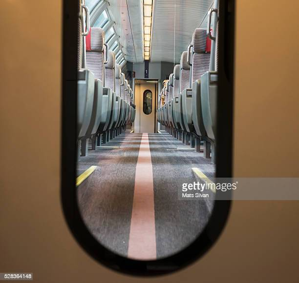 View of seating in a train through the window in a door; Locarno, Ticino, Switzerland