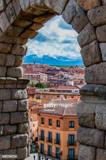 view of segovia through a roman arch - segovia stock pictures, royalty-free photos & images