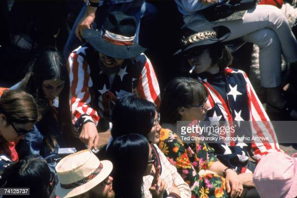 View of several attendees at the Monterey Pop Festival Monterey California midJune 1967 Two men wear matching outfits that include flagbased shirt...