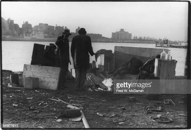 View of several homeless men as they stand and sit near a fire amid debris on the waterfront November 14 1971
