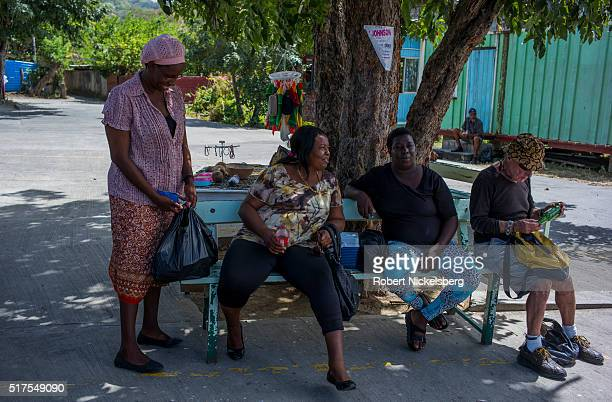 View of several people as they wait on a bench for a transport van in downtown Hillsborough Carriacou island Grenada March 4 2016