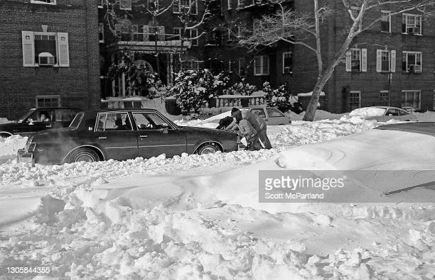 View of several people attempting to free a vehicle from deep snow in the aftermath of a blizzard on 63rd Drive , in the Rego Park neighborhood,...