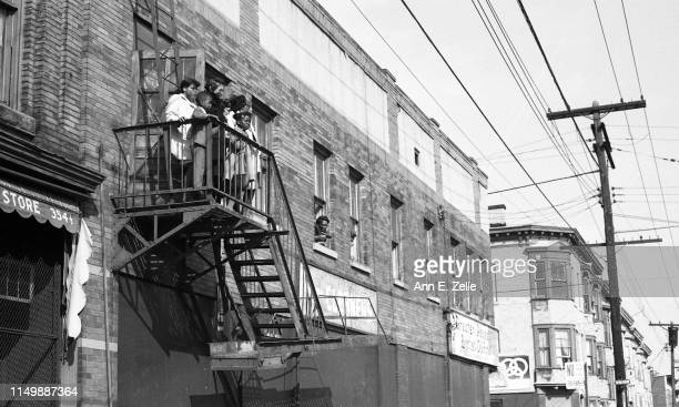 View of several women and children on a fire escape along the route of the 'Walk for Understanding' march through the Central Ward neighborhood on...