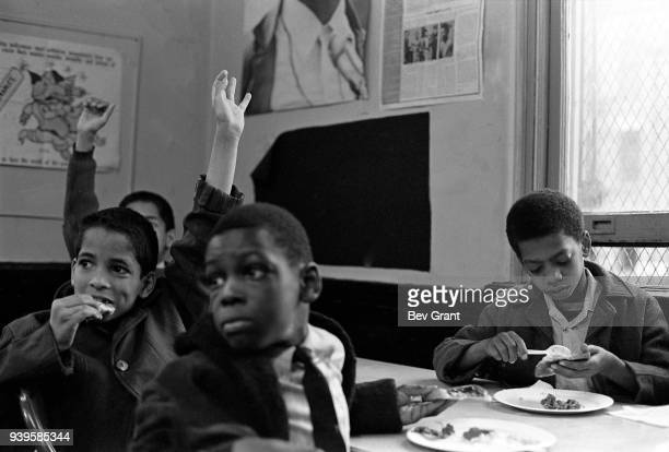 View of several young boys as they raise their hands during a free breakfast for children program sponsored by the Black Panther Party, New York, New...