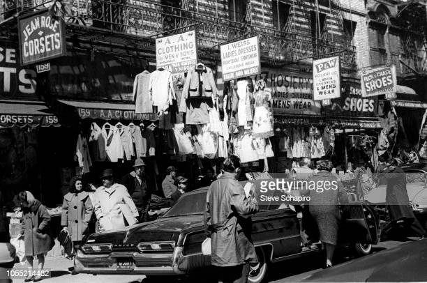 View of shop signs above a crowded sidewalk on Orchard Street on Manhattan's Lower East Side New York New York mid 1960s Visible businesses include...