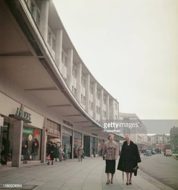 View of shoppers walking along the wide pavement in front of the recently completed Drake Circus shopping centre in Plymouth, England in January 1955.