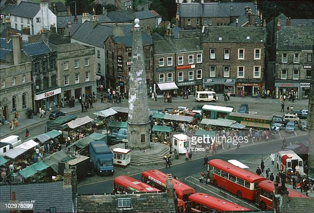 A view of shops and traffic around Richmond marketplace Yorkshire An obelisk which was erected in the 18th century stands at the centre