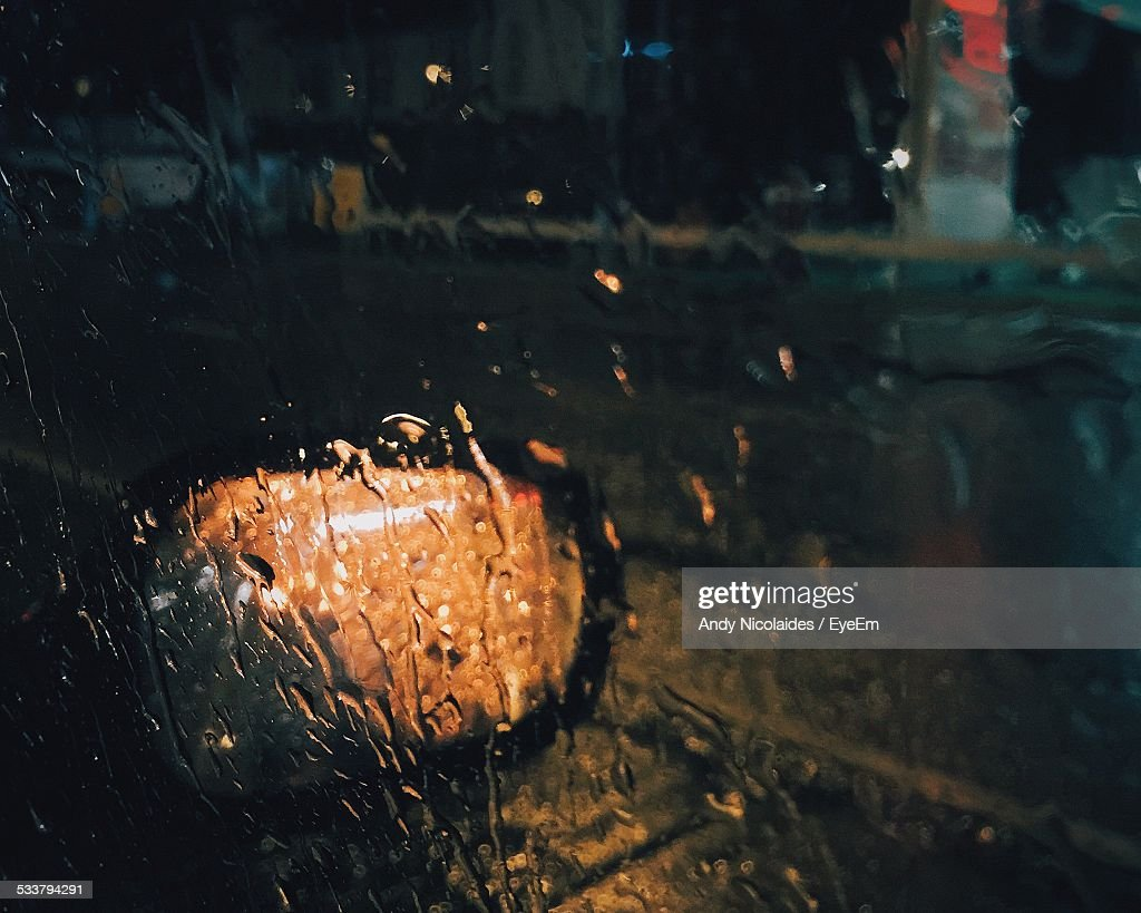 View Of Side-View Mirror Through Wet Window Of Car : Foto stock