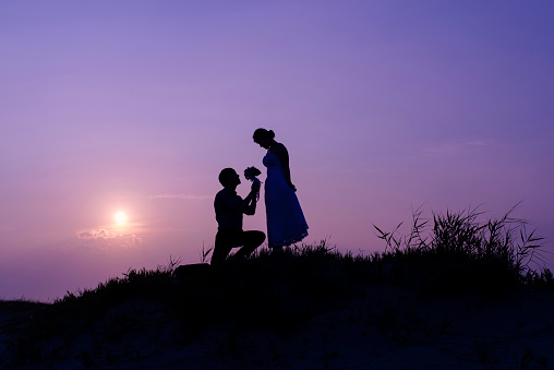 View of silhouette of proposing marriage at night - gettyimageskorea