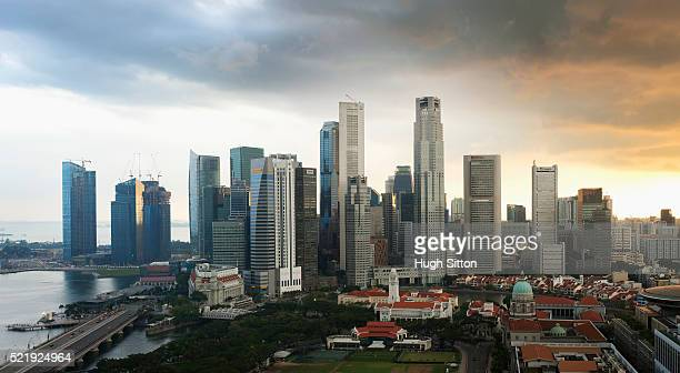 view of singapore business district and harbor with a storm approaching - hugh sitton stock pictures, royalty-free photos & images
