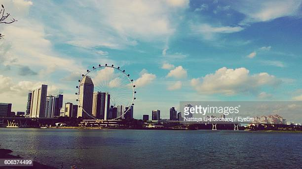 view of singapore flyer and buildings against sky - singapore flyer stock photos and pictures