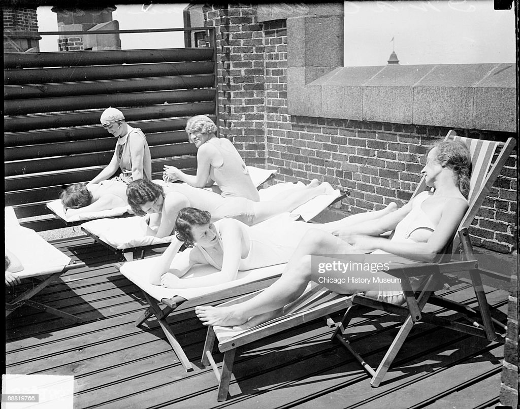 View of six women sitting and lying on lounges on the sun roof of the Women's Athletic Club, located at 626 North Michigan Avenue in the Loop community area of Chicago, Illinois, 1929. From the Chicago Daily News collection.