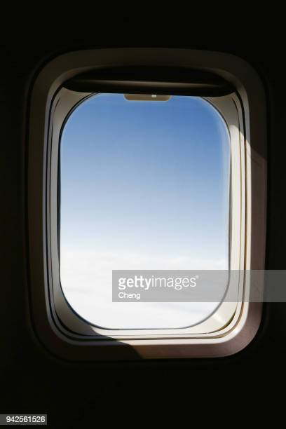 view of sky seen through airplane window - porthole stock photos and pictures