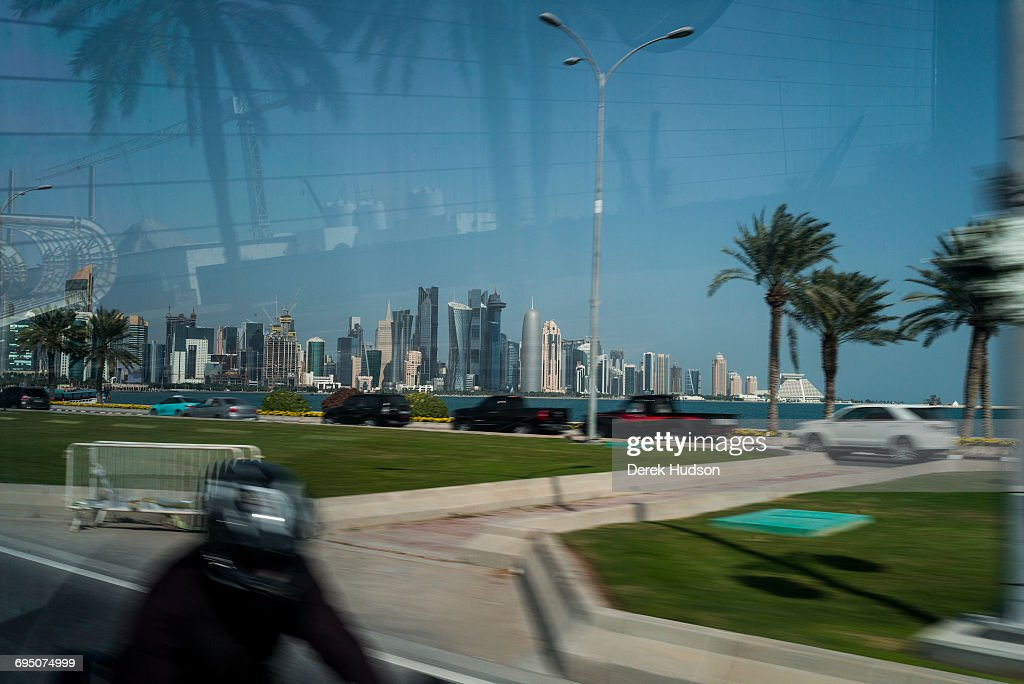 View of skyscraper buildings of the city of Doha as seen from the from the back of a bus driving on the Corniche road.