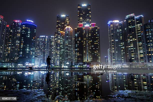 View of skyscrapers at the Marine City residential area in Haeundae District and their reflection in a puddle in Busan, South Korea, at night.
