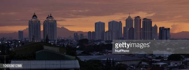 View of skyscrapers with Mount Salak in the background during sunset at Jakarta, Indonesia on February 3, 2019.