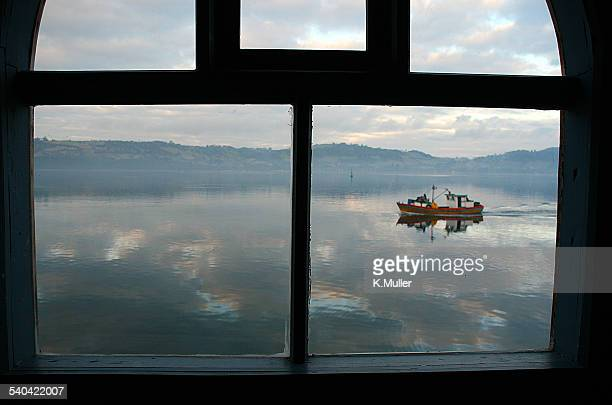 View of small boat on ocean through window