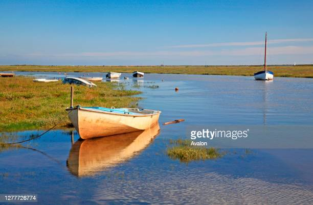 View of small boats moored in a tidal channel in an Area of Outstanding Natural Beauty at Blakeney, Norfolk, England, United Kingdom.