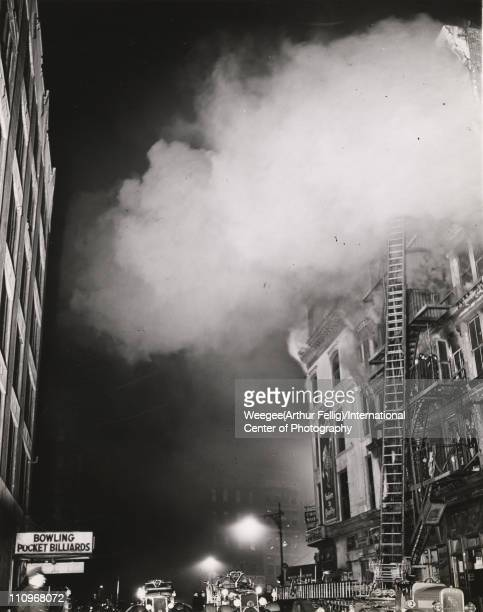 View of smoke as it billows from a burning building and firefighters on the fire escape above a tailor's shop New York New York mid 20th century...