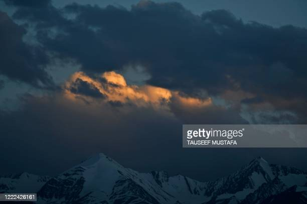View of snow covered mountains as the sun sets in Leh on June 24, 2020. - Indian fighter jets roared over a flashpoint Himalayan region on June 24 as...