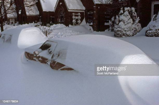 View of snowcovered cars parked on a residential street in the aftermath of a blizzard Queens New York New York February 13 1983