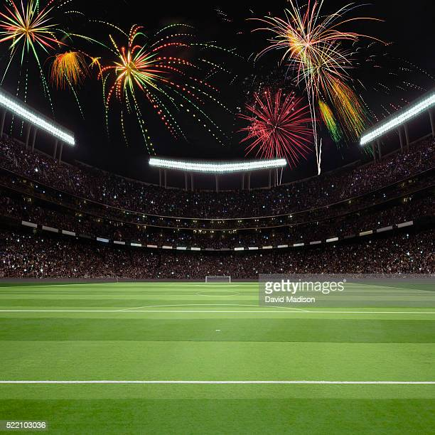 View of soccer field, goal and stadium with fireworks in sky