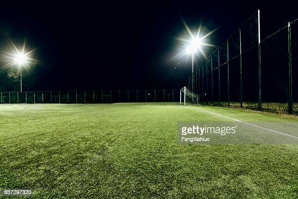view of soccer field illuminated at night - voetbalveld stockfoto's en -beelden