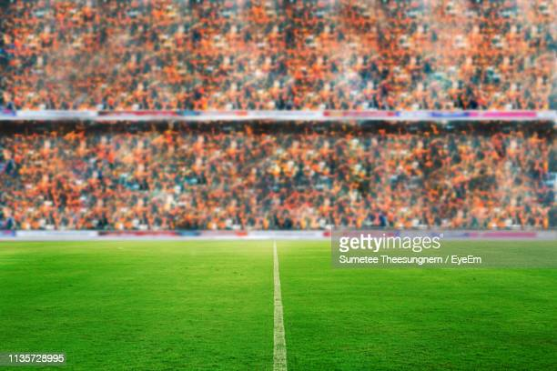view of soccer field with people in background - estádio imagens e fotografias de stock