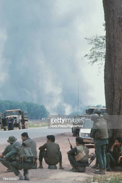 View of South Vietnamese government troops taking cover beside a highway as they watch an amunition dump erupt in flames following a series of...