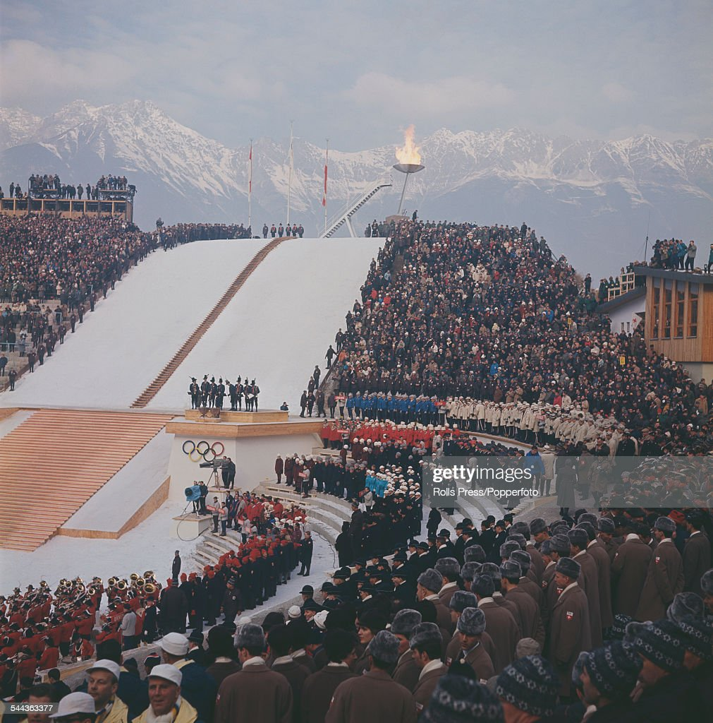 View of spectators, competitors and guests standing together in the ski jump arena with the Olympic flame burning behind during the opening ceremony of the IX Olympic Winter Games at Innsbruck, Austria on 29th January 1964.